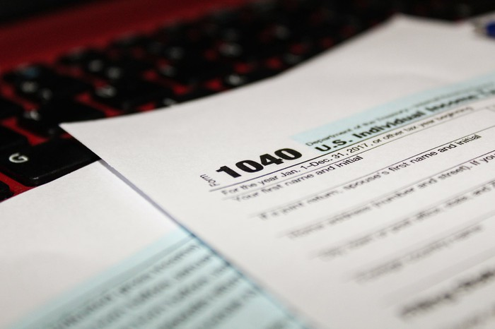 Tax form 1040 laying on a computer keyboard