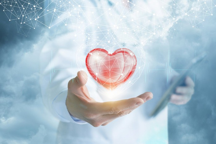 Abstract picture of a doctor with a heart floating above his or her hand.