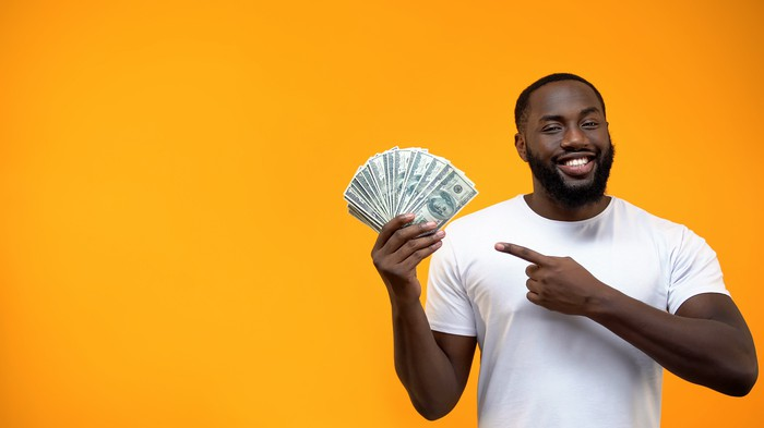 A young man with a beard smiles and points to a handful of dollar bills fanned out in his other hand.