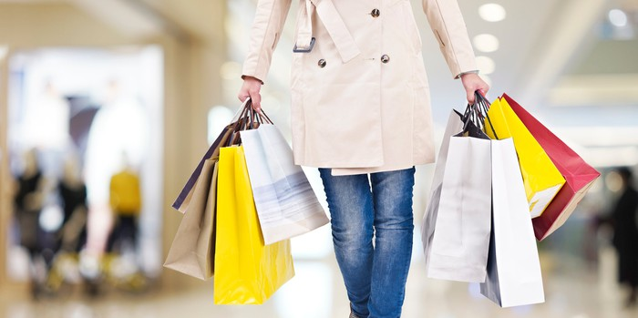 A woman walking through a mall holding shopping bags.