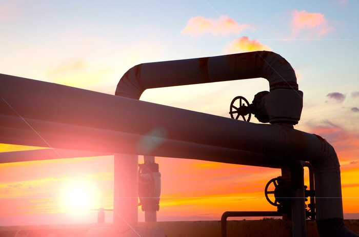 A twist of pipelines with a bright sunset behind them.