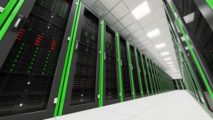 Slanted photo of server racks inside a modern data center, featuring bright green edges on each rack.