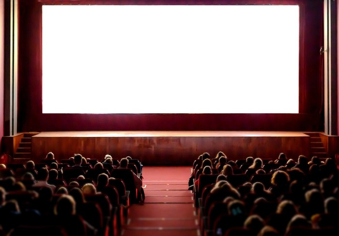 A full movie theater with an empty screen