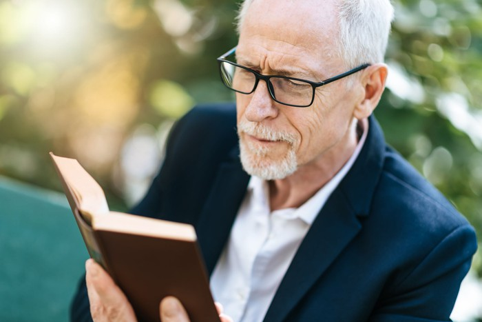 Older man with serious expression reading a book outdoors.