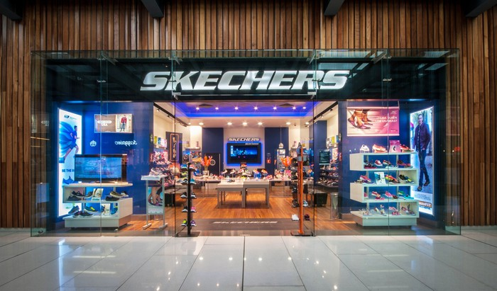 Skechers store front with brightly lit display windows.