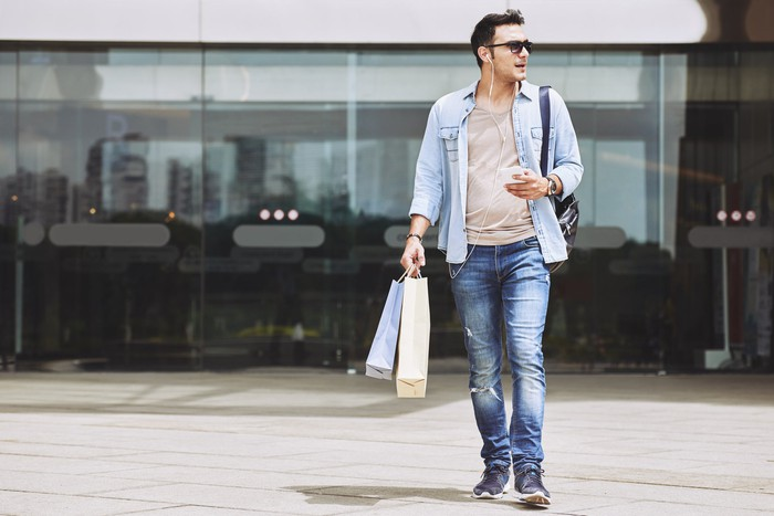 Man leaving shopping mall carrying bags