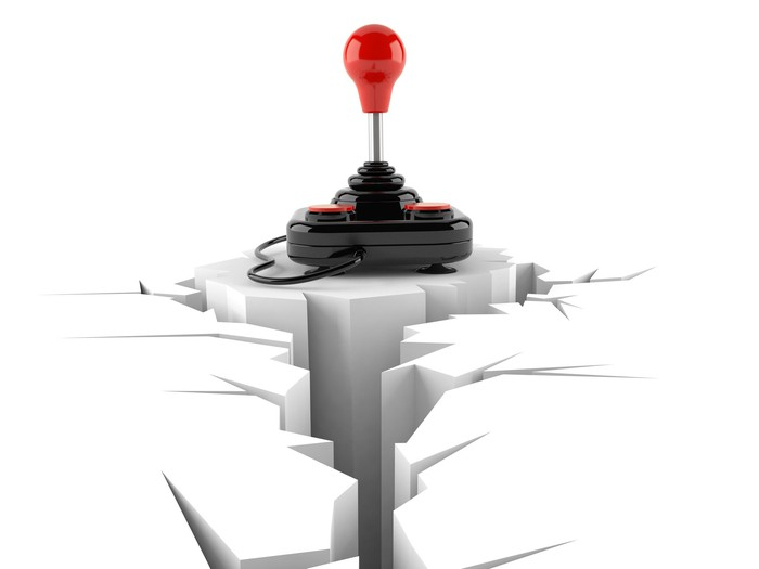 An old-school joystick stands on the edge of a large crack in the white floor.