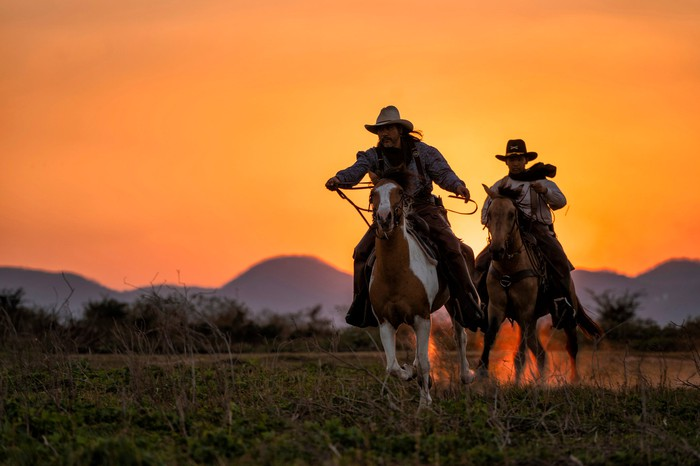 Two cowboys on galloping horses at sunset