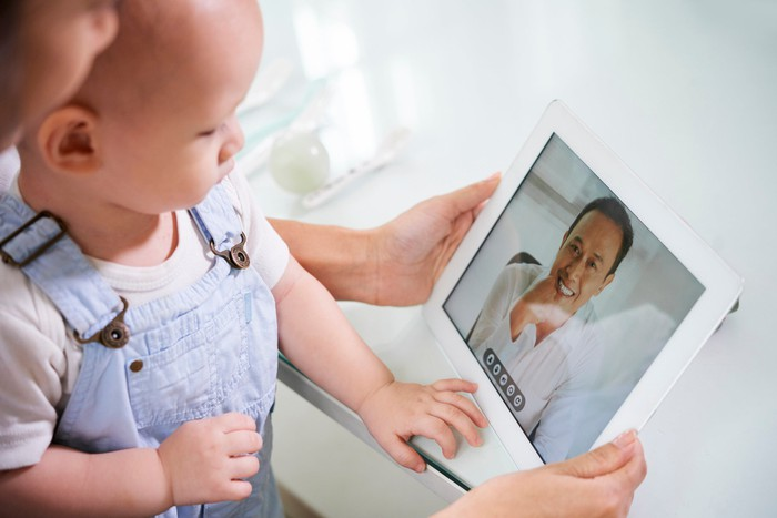 A baby on the lap of another person, both looking at a doctor on a tablet