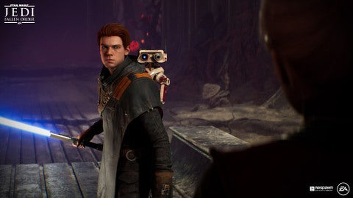 A screenshot from Star Wars Jedi: Fallen Order. A young man accompanied by a small robot is holding a lightsaber.