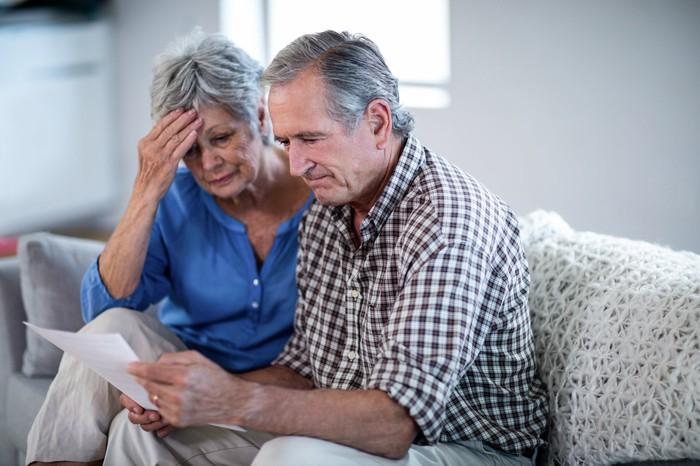 Older man with serious expression holds a document while older woman holds her head and looks on