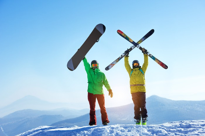 A skier and a snowboarder atop a mountain.