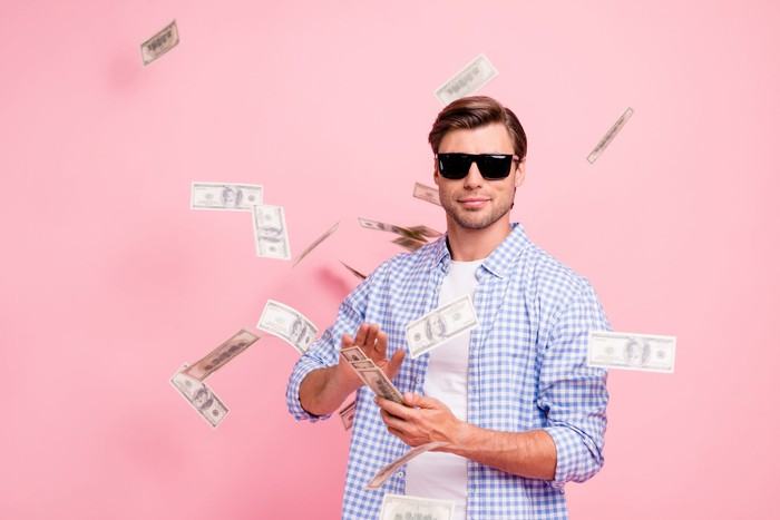 A young man in sunglasses tosses dollar bills in the air like he just doesn't care.