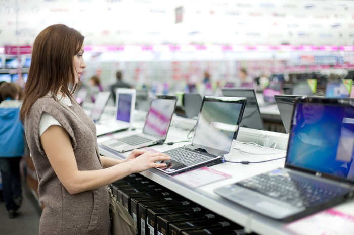 Photograph of woman shopping for a new laptop.