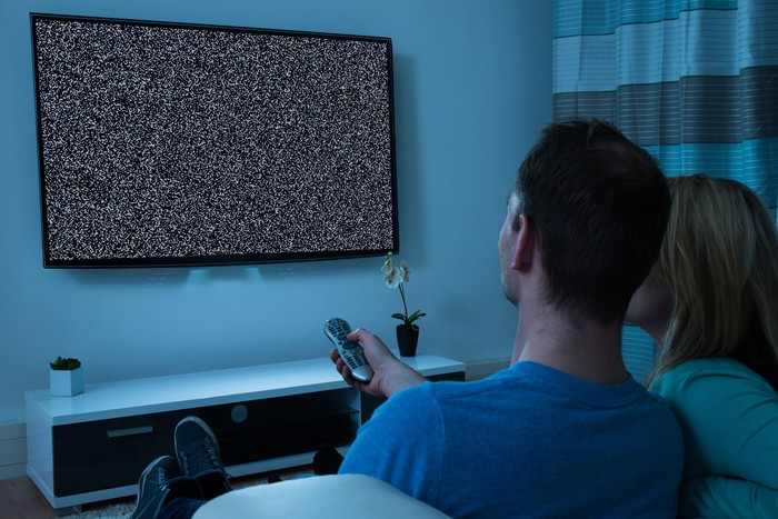 Man and woman sitting in front of blank TV screen