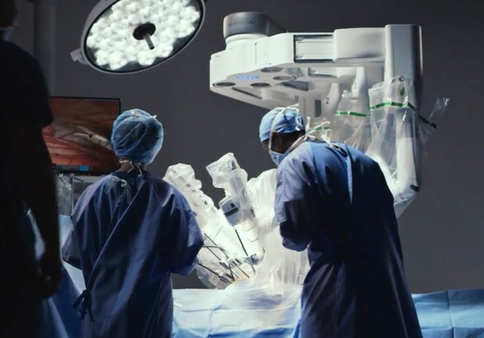 Doctors performing surgery with a daVinci robot.