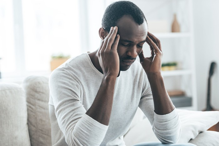 Man holding his head as though in pain