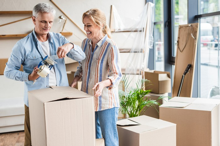 Older man holding packing tape and older woman standing near moving boxes