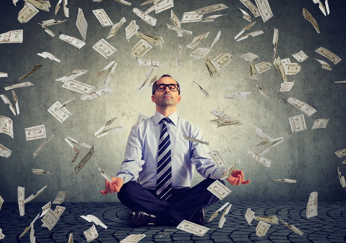 A man in a suit sits in a yoga pose on the floor as dollar bills fall from the sky.