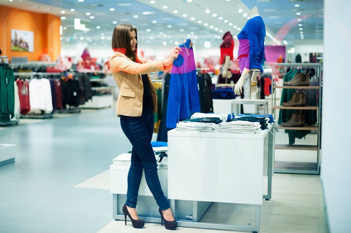 A youngwoman in a department store holding up a blue blouse she is considering