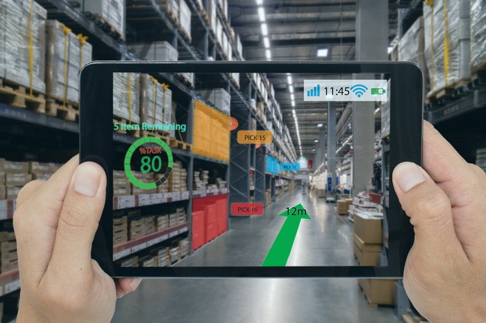 A tablet running an augmented reality app showing virtual graphics being displayed over the camera's view of a warehouse.