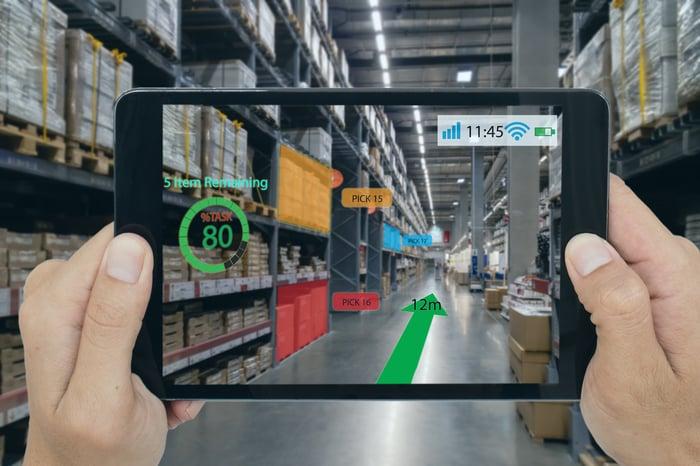 Una tableta que ejecuta una aplicación de realidad aumentada que muestra gráficos virtuales que se muestran sobre la vista de la cámara de un almacén.