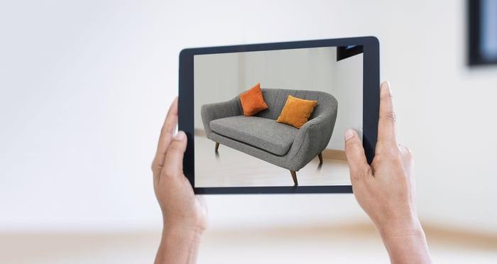 Una pantalla de tableta que muestra cómo se ve un sofá en una habitación vacía utilizando el poder de la realidad aumentada.