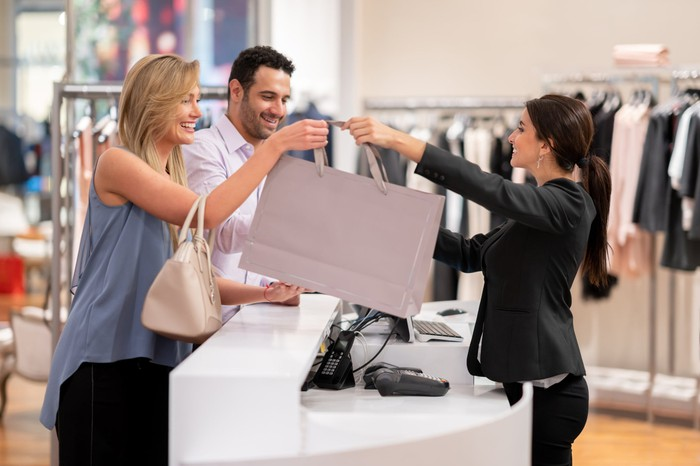 Couple making a purchase at department-store counter from a cheerful store worker