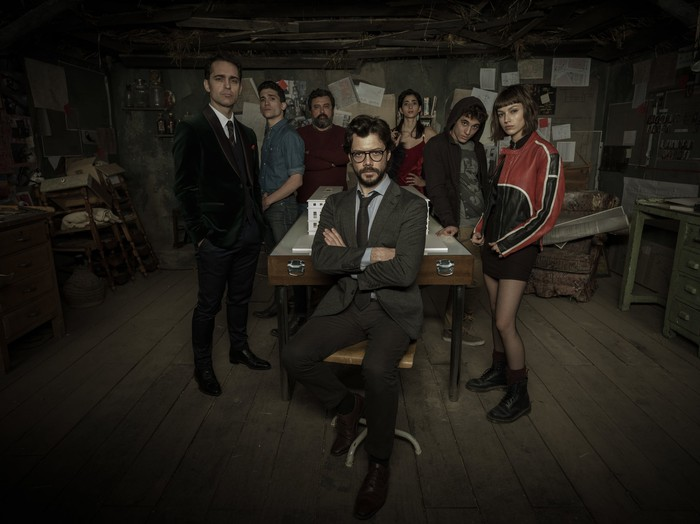 Seven people posing in a dimly lit room.