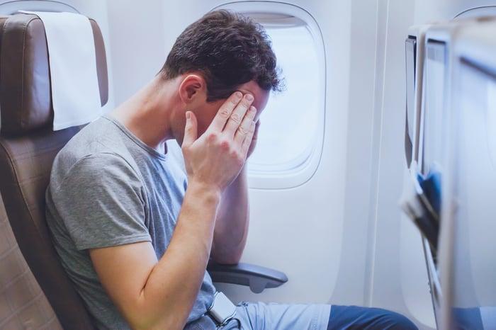 A man suffering a headache aboard an airplane.