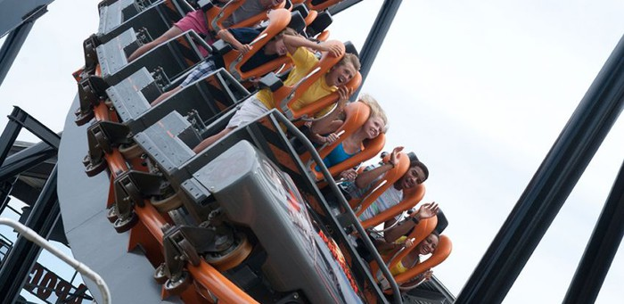 People sitting in a roller coaster car at a Six Flags theme park.