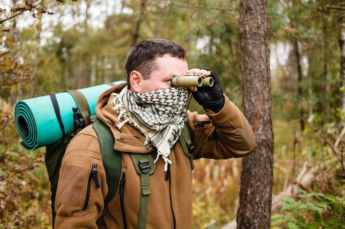 Man in woods looking through binoculars