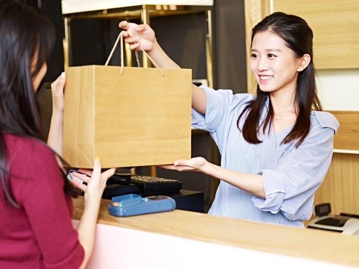 A cashier hands a shopper a shopping bag over the counter.