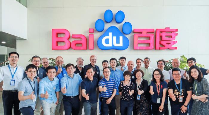 Online researchers posing in front of Baidu's corporate logo.