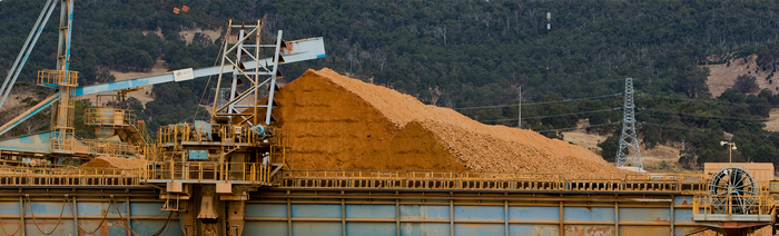 Pile of bauxite raw at a production facility, with cranes and conveyers nearby.