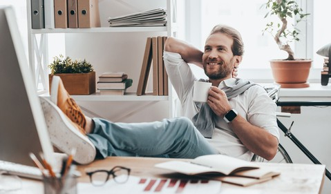 man with feet on desk smiling relaxing thinking