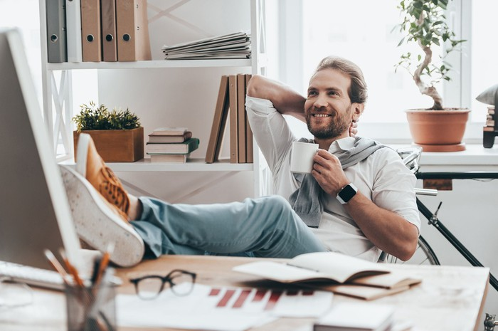 Man looking relaxed in a brightly lit office with a coffee, his feet on the desk, and a smile.