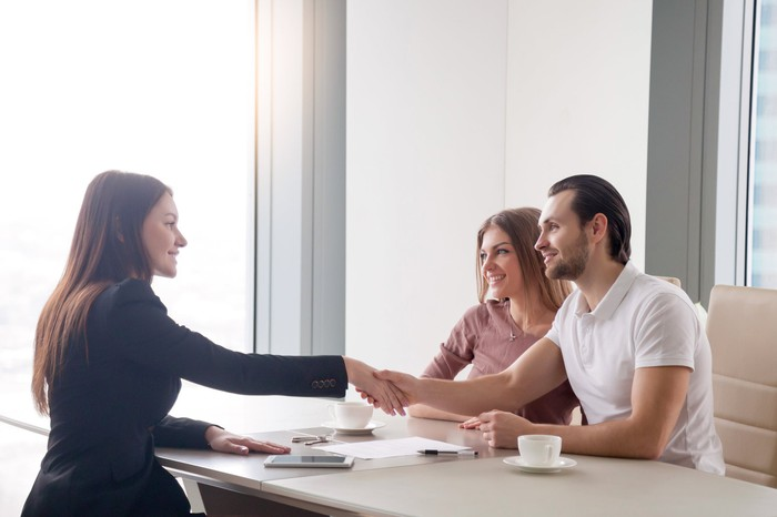 A young couple shakes hands with a banker after signing for a loan.