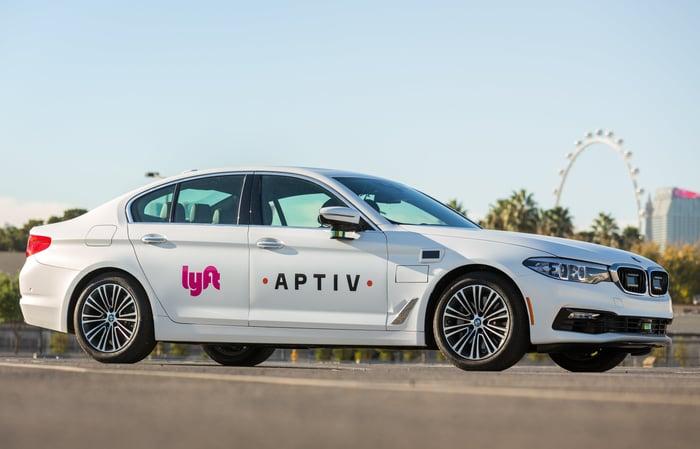 A white BMW sedan with Lyft and Aptiv logos and visible self-driving sensor hardware.