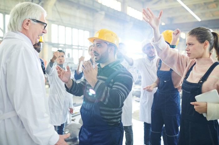 Workers in a plant having a heated discussion in a facility.