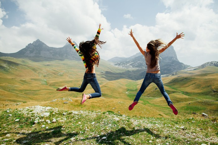 2 women jumping triumphantly in a field.