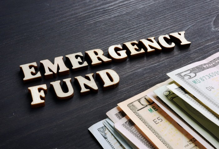 The words 'emergency fund' on a table next to various denominations of bills.