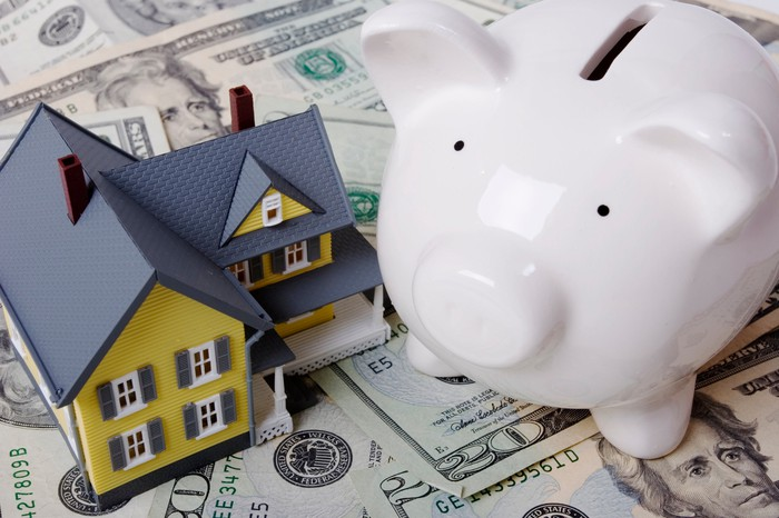 A miniature house and piggy bank seated atop a messy pile of cash.