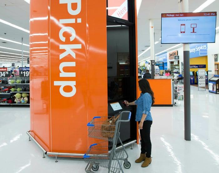 A woman operates a Walmart in-store pickup kiosk.