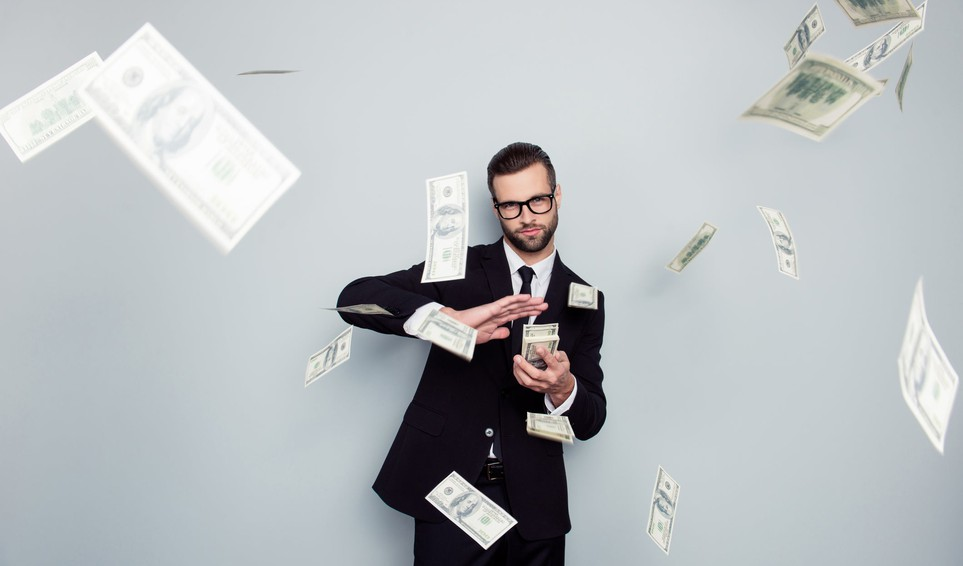 A person in a suit dealing a stack of $100 bills.