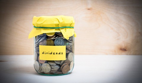 A jar of coins with the word dividneds written on the front.