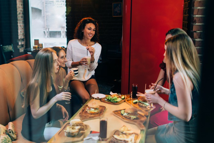Women eating burgers in a fast casual restaurant.