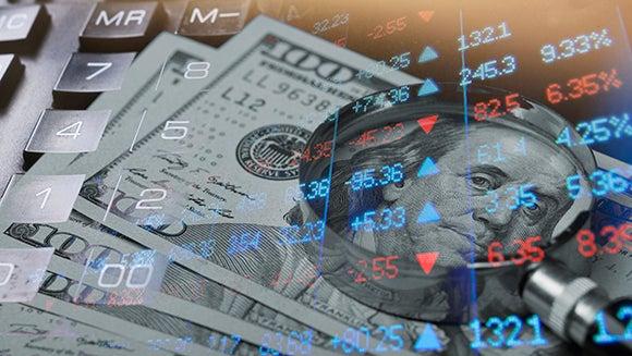 Magnifying glass, stock charts, hundred dollar bills