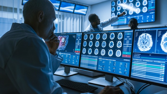 Medical person looking at tumors on multiple computer screens.