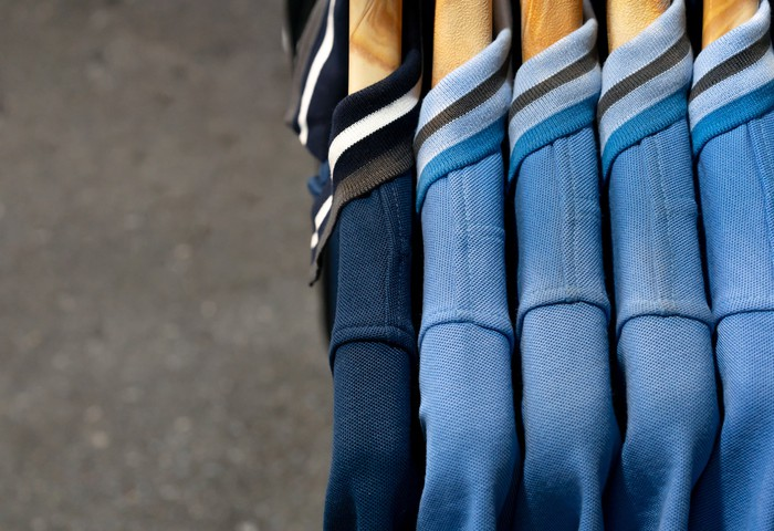 Polo-style shirts in navy and light blue hang on hangers in a shop.